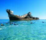 people snorkelling in turquoise water at the 'tangalooma wrecks' shipwrecks at moreton island