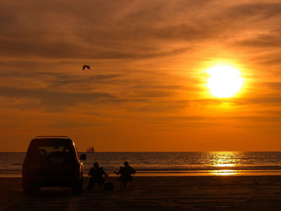 4wd parked on beach at Cable Beach, Broome, people sitting on charis watching sunset