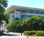 large white parliament house building in darwin from outside with lush green gardens in front of it