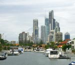 houses with private jettys and boats lining the nerang river with high rise buildings in background at the gold coast