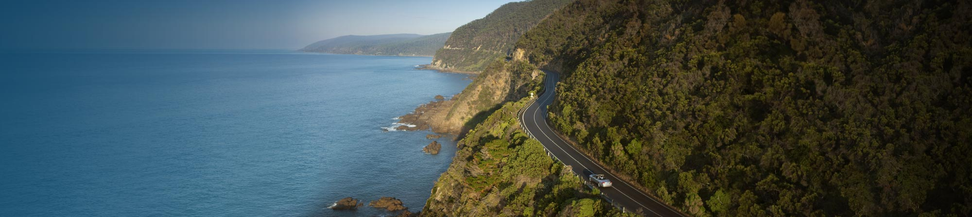 Aerial view of the great ocean road winding along, cut into the side of cliffs that drop into the sea