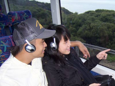 People wearing headsets with GPS triggered commentary units travelling on the Great Ocean Road Adventure coach tour