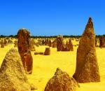 rock spire sticking out of bright yellow sand with intense blue sky at pinnacles desert.