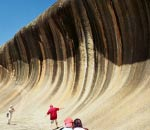 man pretending to surf with wave rock rising up behind him