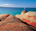 man stands on red rust coloured rocks looking over azure to turquoise coloured water at bay of fires