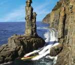 boat travels narrow ocean passage between cliffs and island rock spire near bruny island tasmania
